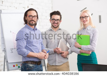 Successful group of business people in office. Happy people looking at camera while working. People on glasses are business colleagues. - stock photo
