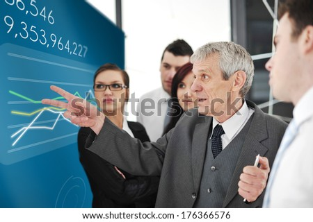 Successful group of businesspeople headed by senior manager analyzing stock market on large digital display - stock photo