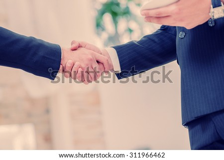 Successful handshake. Two successful businessman standing in the restaurant and drink coffee while shaking hands with each other close-up view of hands - stock photo