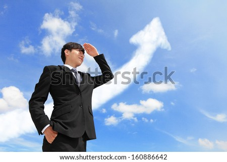 Successful handsome business man purposefully looking away with arrow cloud and blue sky, model is a asian male