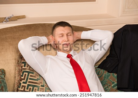 successful handsome man sitting on the couch after work. young businessman put his hands behind his head, resting and smiling