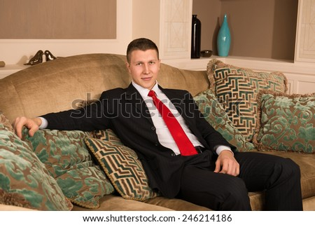 successful handsome man sitting on the couch. young businessman resting after work in his posh apartment. man in a business suit - stock photo