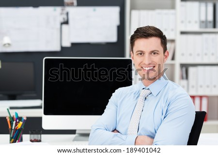 Successful handsome young businessman with a happy smile sitting at his desk in the office with folded arms - stock photo