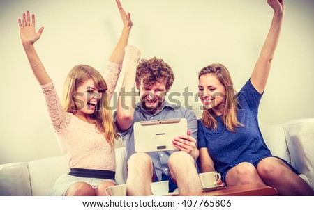 Successful happy friends with hands up browsing surfing internet on tablet. Young people man guy and women girls sitting on sofa relaxing at home.