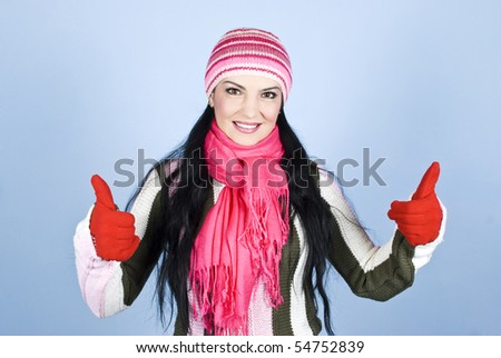 Successful happy winter woman giving thumbs up with gloves in hands and smiling for you in front of blue background - stock photo