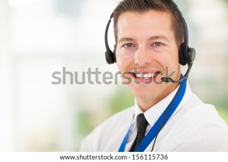 successful male call centre employee wearing a headset - stock photo
