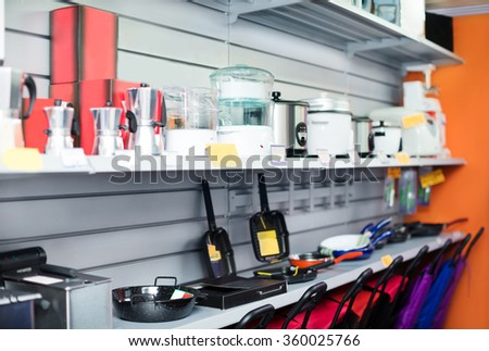 Successful male seller in household appliances section of supermarket  - stock photo