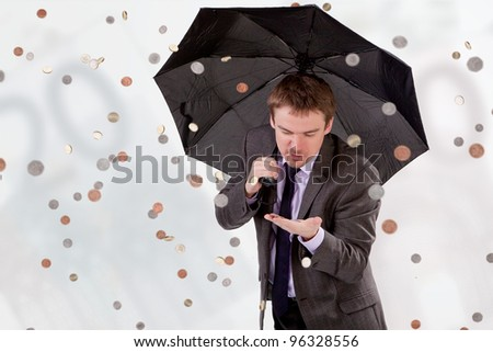 Successful man counting money that fell from the sky - stock photo