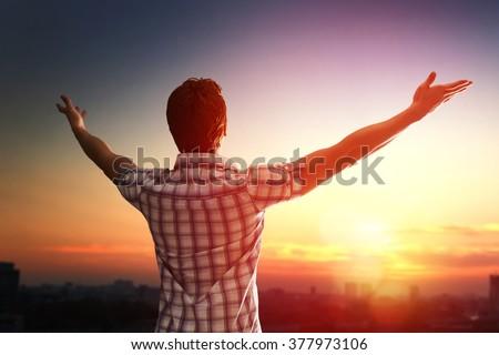 Successful man looking up to sunset sky celebrating enjoying freedom. Positive human emotion feeling life perception success, peace of mind concept. Free happy man - stock photo
