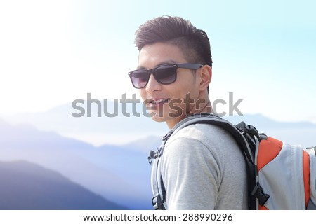 Successful man mountain hiker with backpack on the top of mountains. asian