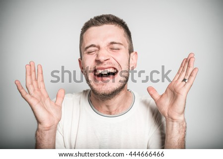 successful man rejoices victory with his fists, isolated on a gray background