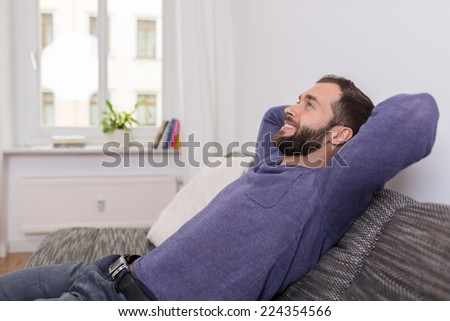 Successful man relaxing on the sofa at home sitting with his hands clasped behind his head and a huge contented smile pf pleasure - stock photo