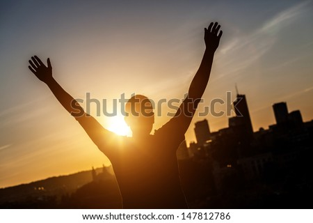 Successful Man with Raised Arms at Sunset - stock photo
