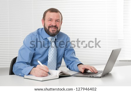 successful mature business man smiling and working on laptop - stock photo