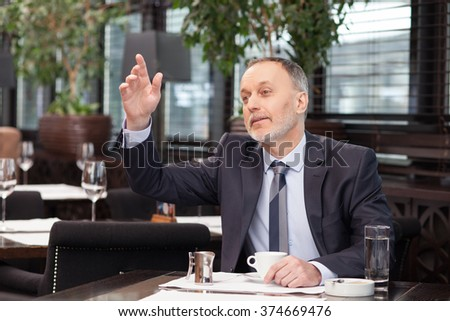 Successful mature businessman is calling the waiter in cafe. He is raising his arm and smiling. The worker is sitting at the table and looking forward with anticipation - stock photo