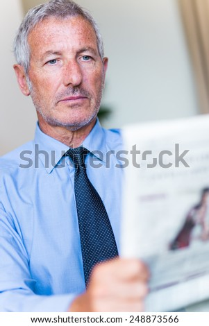 Successful mature handsome businessman reading the newspaper - stock photo
