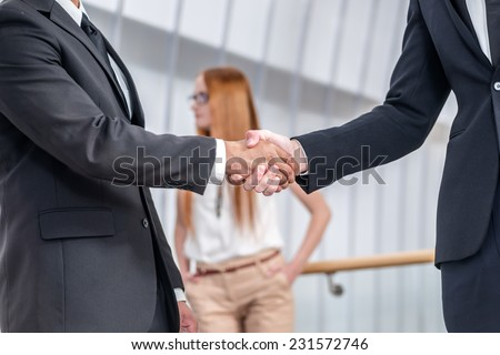 Successful meeting. Two Confident businessman firmly shake hands with each other while two colleagues talking in the background - stock photo