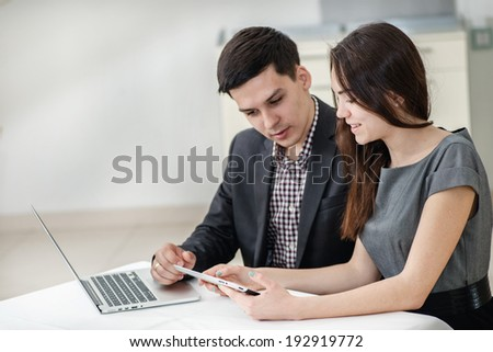 Successful meeting! Young businesspeople sitting at the table and talk to each other. Confident young people smile at each other and work for a laptop and a tablet. Guys sitting in a restaurant - stock photo