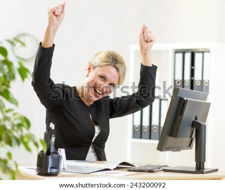 Successful middle-aged business woman with arms up in office