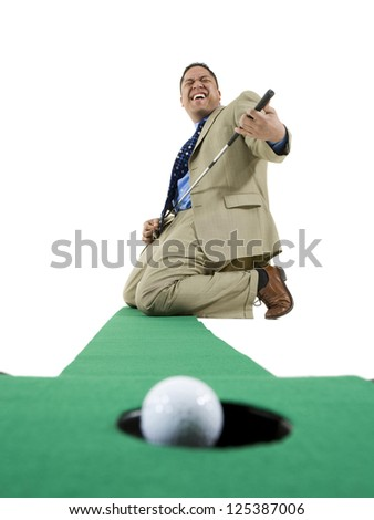Successful mini golf player kneeling in business suit playing air guitar - stock photo