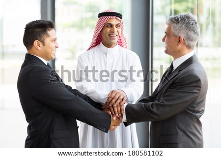 successful multicultural global business team hands together - stock photo
