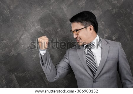Successful of businessman. Asian man wear glasses in grey suit with hand up on grey background texture.