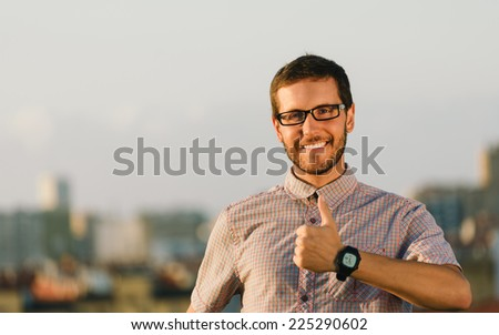 Successful professional casual man doing thumbs up gesture with city on background. Entrepreneur enjoying job success. - stock photo