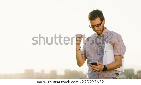 Successful professional casual man gesturing and checking cellphone messages towards city skyline. Entrepreneur enjoys success in job. - stock photo