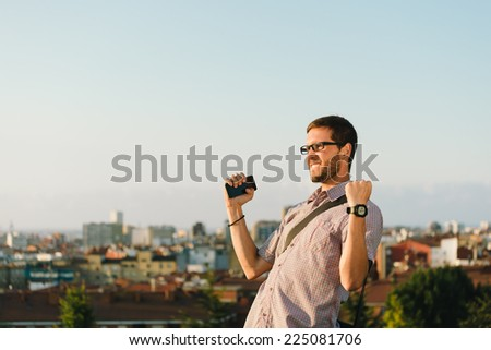 Successful professional casual man gesturing towards city. Entrepeneur enjoys success in job. - stock photo