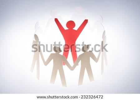 Successful red paperman surrounded by team representing unity isolated over gray background - stock photo