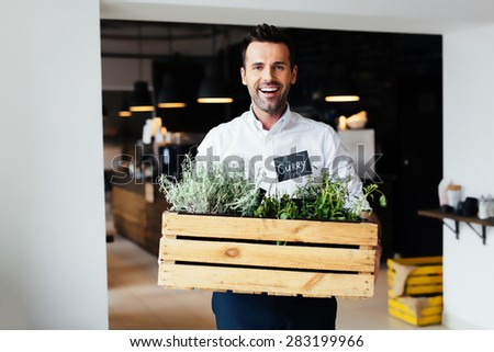 Successful restaurant manager holding box with fresh spices - stock photo