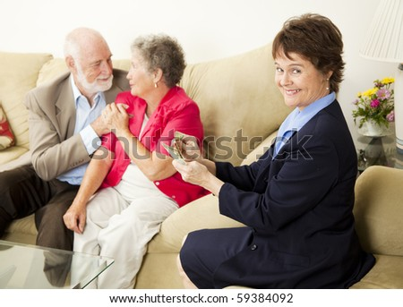 Successful saleswoman counting her money in the home of satisfied customers. - stock photo