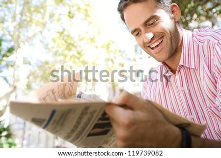 Successful senior businessman reading a financial newspaper while sitting in a classic city square, outdoors. - stock photo