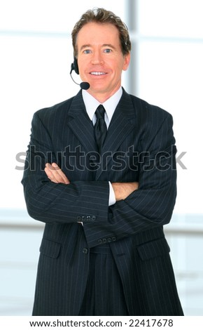 successful senior caucasian businessman wearing headset as he fold his arm