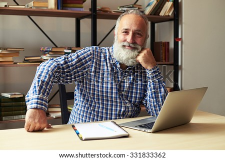 successful senior man sitting at his working place, looking at camera and smiling