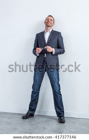 successful serene handsome 40s businessman leaning on the office wall, holding his cool eyeglasses, relaxing for a modern corporate portrait, white background studio - stock photo