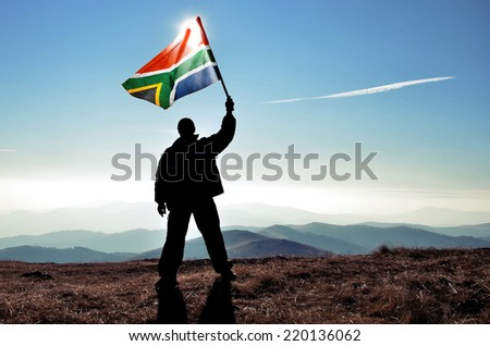 successful silhouette man winner waving South African flag on top of the mountain peak - stock photo