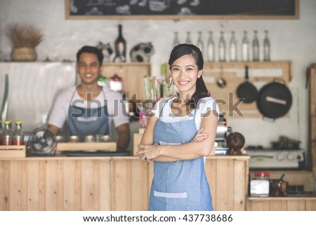 Successful small business owner standing with crossed arms with partner at the background