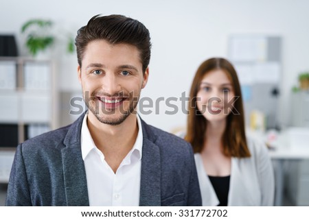 successful smiling businessman with female co-worker in background - stock photo