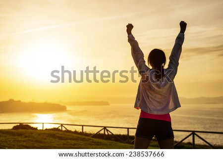 Successful sporty woman raising arms towards golden beautiful sunset and sea. Female athlete celebrating sport success and goals. Healthy lifestyle and freedom concept. - stock photo