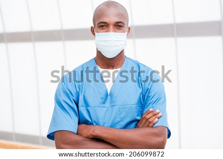 Successful surgeon. Confident young African doctor in blue uniform and surgical mask looking at camera and keeping arms crossed - stock photo
