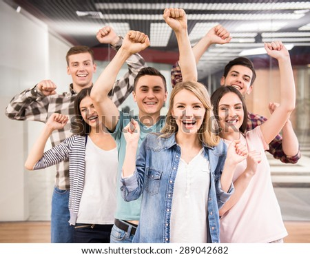 Successful team. Group of cheerful young people standing close to each other and enjoying success. - stock photo