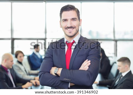 Successful team leader and business owner proudly standing with crossed arms with  coworkers working in office in background. Business and entrepreneurship concept. - stock photo