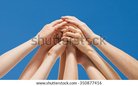 Successful team: many hands holding together  on sky background - stock photo