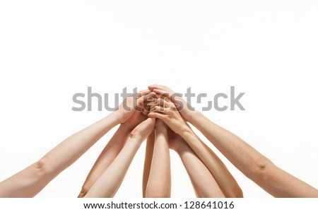 Successful team: many hands holding together on white background - stock photo