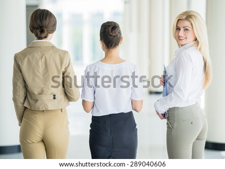 Successful team of business ladies moving together at office. Back view. - stock photo