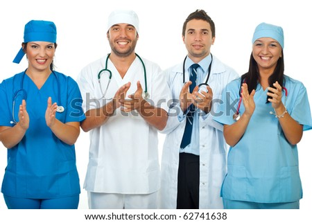 Successful team of four different doctors applauding together isolated on white background - stock photo
