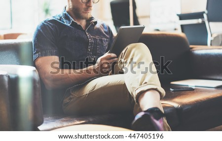 Successful Trade Manager reading business news modern Interior Design Loft Office.Man relaxing Vintage Sofa,Use contemporary tablet,browsing Internet.Blurred Background.New Startup Idea Process - stock photo