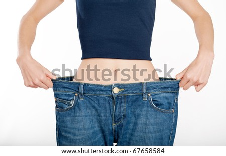 Successful weight loss, woman with too large jeans after a diet - stock photo