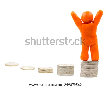 Successful winner on the top - self-made human plasticine figure standing on top of a stack of coins - stock photo